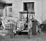 Libesice, Czech republic - May 19, 2018: wreck of old tractor in front of house in Libesice village during spring sunrise with bla. Ck and white stylization Stock Photo