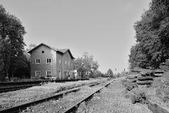 Libesice Tjeckien - Maj 19, 2018: järnvägsspår som leder mellan träd och byggnad för drevstation under vårsoluppgång med Arkivbild