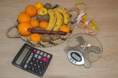 Fruits, Libra, calculator and centimeter on a wooden table. Libra, calculator and centimeter on a wooden table. Diet concept Royalty Free Stock Images