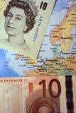 Libra esterlina británico y billetes de banco euro en mapa europeo Fotografía de archivo