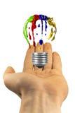 Libración pintada de la bombilla sobre la mano Imágenes de archivo libres de regalías