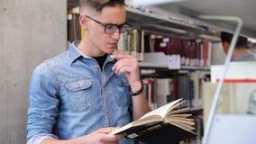 librairie Étagères de Reading Books Near d'étudiant d'homme banque de vidéos