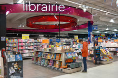 Librairie. BELGIUM - OCTOBER 2014:  Boy is reading a comic book at the librairie section in a Carrefour hypermarket in Belgium Stock Image