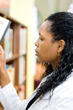 Librarian. An attractive young african female student librarian working in library Stock Photos
