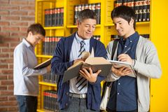 Librarian Assisting Student In College Library Stock Images