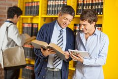 Librarian Assisting Student In University Library. Happy mature male librarian with book assisting student in university library royalty free stock photos