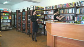 Librarian finds textbook for student at library stock video