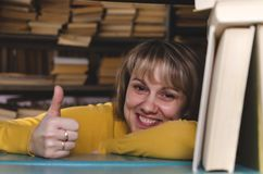 Librarian. Happy woman a librarian is looking through a bookshelf in a library and is showing a thumbs up royalty free stock photos