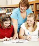 Librarian Helps Students. Teacher or librarian in the school library, helping teenage students with their homework Stock Image