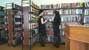 Librarian helps to find books for young woman stock video footage