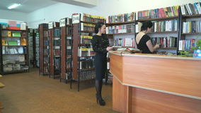 Librarian helps to find books for young woman stock video