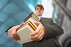 Librarian holding pile of books. A librarian holding a big pile of books Royalty Free Stock Image