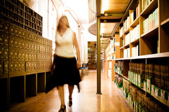 Librarian in a library aisle. Blurred motion picture of a librarian moving through a library aisle, passing by old-fashioned index cabinets Royalty Free Stock Photography
