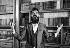 Librarian in the library. Going crazy, mad and insane, wild, stress and agression. Shame, hysteria, accuse, blame, fault, rage responsibility uncontrollable stock photo
