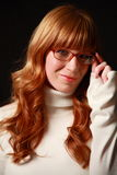 Librarian look. Attractive natural red haired woman with added highlights shows off her spectacles Royalty Free Stock Images