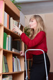 Librarian rearranges books Stock Image