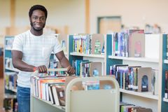 Librarian With Trolley Of Books In Bookstore. Portrait of African American librarian with trolley of books in bookstore Stock Images