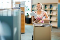 Librarian With Trolley Of Books In Library. Portrait of smiling female librarian with trolley of books in library Stock Image