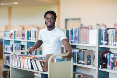 Librarian With Trolley Of Books In Library. Portrait of young male librarian with trolley of books in library Royalty Free Stock Image