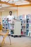 Librarian With Trolley Of Books Smiling In. Portrait of African American librarian with trolley of books smiling in bookstore Royalty Free Stock Photos