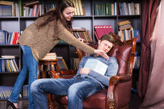 Librarian trying to wake a sleeping man Royalty Free Stock Image