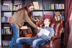Librarian waking a sleeping man in the library. Librarian waking a sleeping men in the library stretching down to retrieve the open book on his chest as he takes Royalty Free Stock Photo