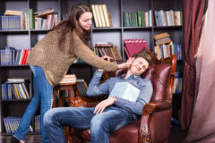 Librarian waking a sleeping man in the library. Librarian waking a sleeping men in the library touching him gently on the cheek as he dozes in a leather armchair Stock Image