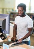 Librarian Working At Counter In Bookstore. African American male librarian working at counter in bookstore Royalty Free Stock Photo