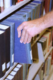 Library. Man selecting book from shelf in library Stock Photos