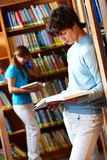 At library. Tilt up shot of two teens reading books at library Stock Photography