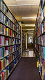 The library with colorful books on the shelves. An alley in the library surrounded with colorful bookshelves Royalty Free Stock Photo