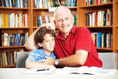 Library - Annoying Dad. Annoying father teasing his son when they are supposed to be studying at the library stock photos