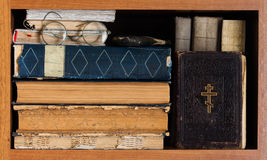 Library book shelf with Holy Bible book, aged books covers, spectacles. Vintage wooden frame. Christianity concept image Stock Photography