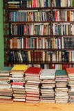 Library books. Large pile of old books with library shelves in the background Royalty Free Stock Photo