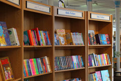 Library books on shelves-Kids fiction. A row of shelves with books on titles Kids fiction. Various books for children for sale Stock Image
