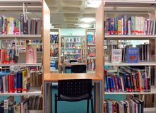 Library books on shelves and study area. A public library with rows of shelves with books on. Seats for studying and reading books Royalty Free Stock Photography
