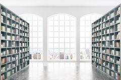 Library with city view. Library interior design with massive bookshelves, concrete floor and city view. 3D Rendering Stock Photo