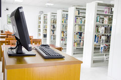 Library and computer. A computer and many book shelves  in a library Stock Image