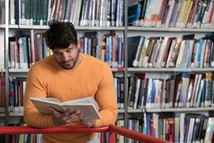 Happy Male Student Reading from Book in Library. In the Library - Handsome Male Student With Books Working in a High School - University Library - Shallow Depth Stock Image