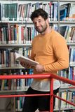 Happy Male Student Reading from Book in Library. In the Library - Handsome Male Student With Books Working in a High School - University Library - Shallow Depth Royalty Free Stock Image