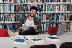 Happy Male Student With Laptop in Library. In the Library - Handsome Male Student With Laptop and Books Working in a High School - University Library - Shallow Royalty Free Stock Photo