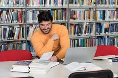 Student Learning in Library. In the Library - Handsome Male Student With Laptop and Books Working in a High School - University Library - Shallow Depth of Field Stock Photography