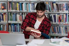 Student Studying at College. In the Library - Handsome Male Student With Laptop and Books Working in a High School - University Library - Shallow Depth of Field Royalty Free Stock Photos