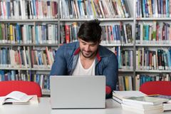 Male Student Typing on Laptop in the University Library. In the Library - Handsome Male Student With Laptop and Books Working in a High School - University Royalty Free Stock Images