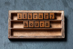 Library hours conept. Vintage blocks with letters, aged wooden box. Gray stone background, macro, soft focus Stock Image