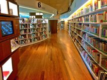 Library interior with book shelves. Modern interior design of Library@Orchard in Singapore, with avant-garde curvy bookshelves and LCD screens Royalty Free Stock Image