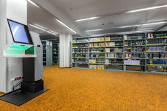 Library interior with modern technology. Stylish library interior with orange flooring and modern device for lending books royalty free stock photography