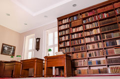 Library interior. A shot of library interior with big bookshelf, tables, picture, wall clock and windows in the background stock photos