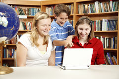 Library Kids on Netbook Computer. Two teen girls and a younger boy using a netbook computer in the school library Royalty Free Stock Photo