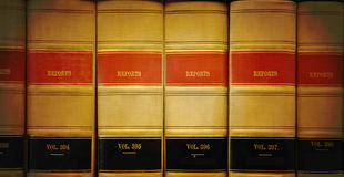 Library Law Books. A closeup of old looking law books in a library on a shelf. The lighting is on the center. Colors are brown, red and black Stock Photo